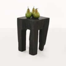 black teak root table with green apples angle view