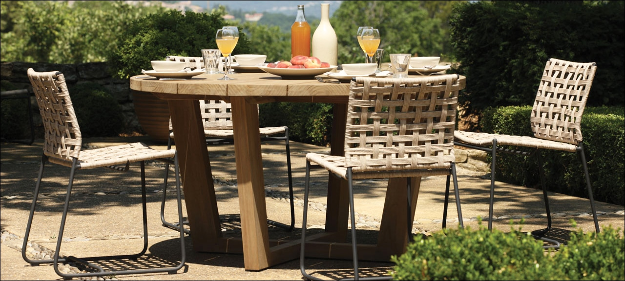 Outdoor wooden dining table with four wicker style chairs